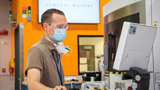 Manufacturing engineer Benjamin LeBlanc inspects a 3D printer at the GM Additive Industrialization Center in Warren, Michigan.